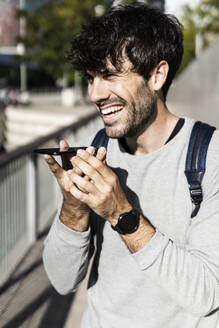 Happy man using smartphone in the city - GIOF07232