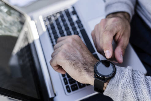 Close-up of man with smartwatch and laptop - GIOF07244