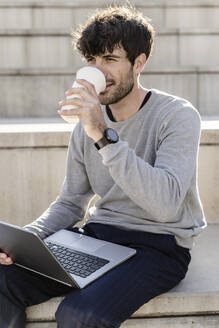 Man sitting on outdoor stairs with takeaway coffee and laptop - GIOF07247