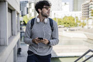 Man with smartphone in the city on the go - GIOF07253
