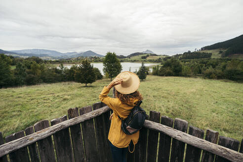Young woman wearing yellow coat and backpack with a hand holding a hat in her head looking the lake landscape on top of a wood balcony - MTBF00001