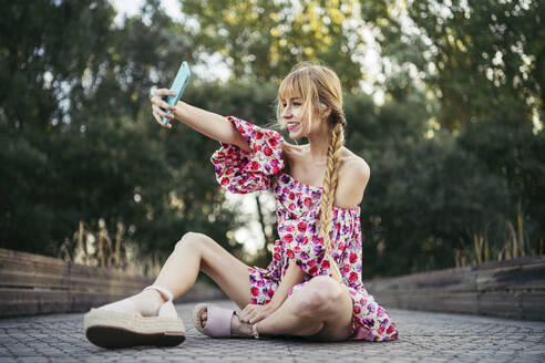 Portrait of smiling young woman  sitting on boardwalk in summer taking selfie with smartphone - MTBF00022