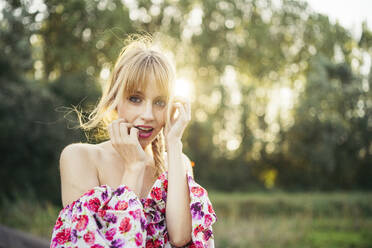 Portrait of blond young woman wearing summer dress with floral design at backlight - MTBF00028