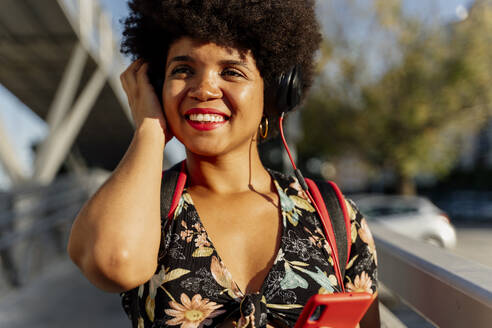 Female Afro-American with headphones and smartphone listening music, looking sideways - ERRF01726