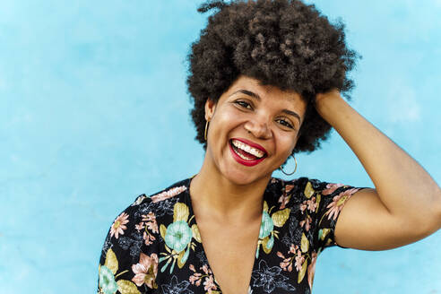 Portrait of smiling female Afro-American woman, hand in hair - ERRF01762