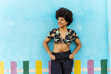 Smiling Afro-American woman in front of a blue wall looking sideways - ERRF01765
