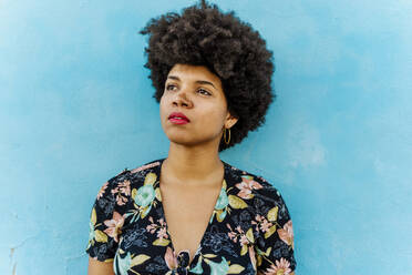 Portrait of Afro-American woman looking sideways, blue wall in the background - ERRF01771