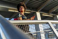 Smiling Afro-American woman with red smartphone - ERRF01774