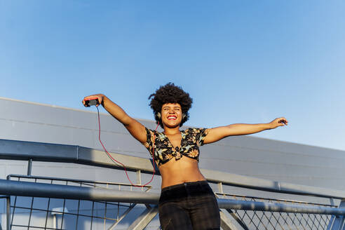 Smiling Afro-American woman with red smartphone - ERRF01780