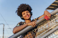 Smiling Afro-American woman with red smartphone and headphones - ERRF01786