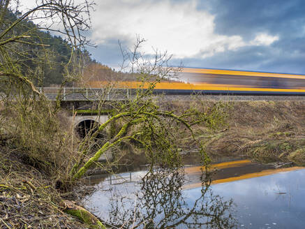 Germany, Bavaria, Long exposure of train passing pond in Upper Palatinate Forest - HUSF00084