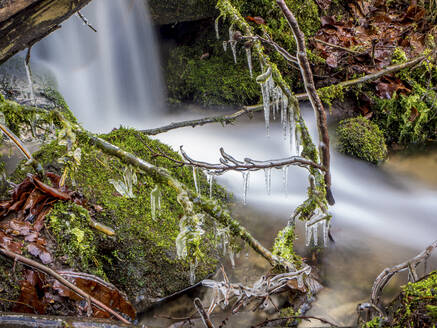 Germany, Bavaria, Ice-covered branches against splashing waterfall - HUSF00090
