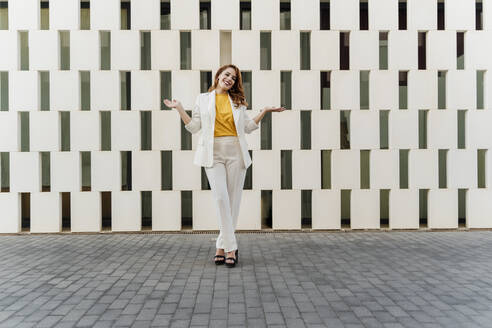Businesswoman in white pant suit, standing in front of facade, gesturing - ERRF01816