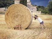 Little girl rolling hay bale - XCF00290