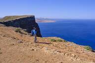 Frau mit Rucksack steht am Klippenrand, Ausblick von Risco de Famara, Lanzarote, Kanarische Inseln, Spanien - SIEF09169
