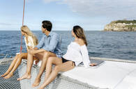 Three young friends enjoying a summer day on a sailboat - MGOF04146