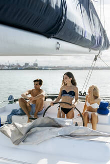 Three young friends enjoying a summer day on a sailboat - MGOF04158