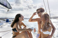 Three young friends enjoying a summer day on a sailboat - MGOF04167