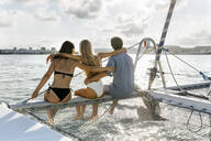 Three young friends enjoying a summer day on a sailboat - MGOF04191