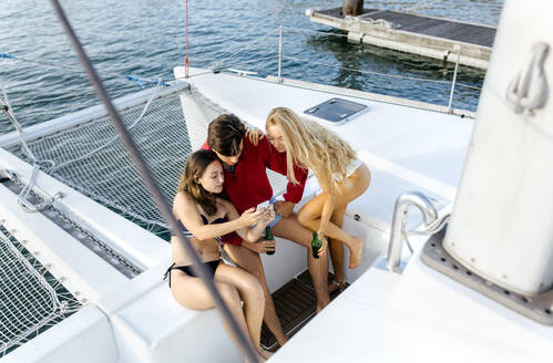 Three young friends enjoying a summer day on a sailboat, taking a selfie - MGOF04203