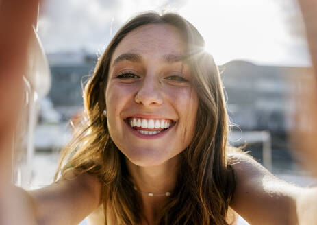 Young beautiful woman taking a selfie on a sailboat - MGOF04209