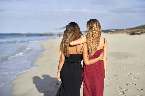 Two young women standing arm in arm on a beach - EPF00626