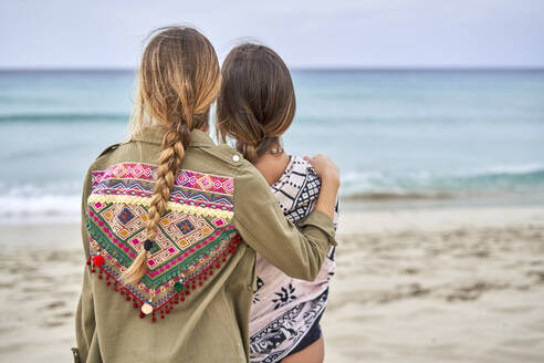 Rear view of two young women standing close to each other on a beach - EPF00638