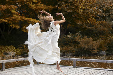 Ballerina wearing white dress and jumping on wooden jetty - FCF01824