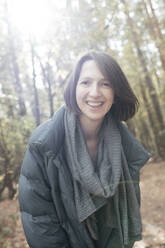 Portrait of smiling woman in autumnal forest - EYAF00615