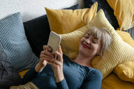 Portrait of smiling woman lying on the couch using smartphone - KNSF06826