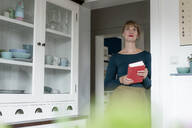 Portrait of woman with novel lening against door case at home - KNSF06835