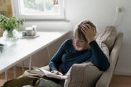 Woman sitting on couch reading a novel - KNSF06838