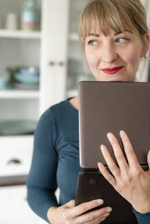 Portrait of smiling woman with laptop in the kitchen looking at distance - KNSF06847