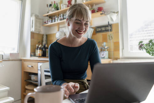 Portrait of happy woman sitting in the kitchen using laptop - KNSF06850