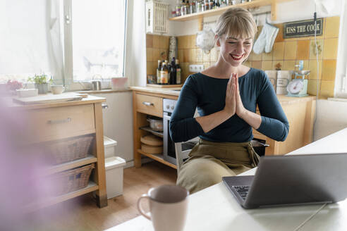 Portrait of laughing woman with laptop practicing yoga in the kitchen - KNSF06853