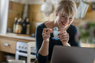 Portrait of laughing woman with little robot and laptop in the kitchen - KNSF06856
