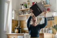 Portrait of screaming woman with laptop in the kitchen - KNSF06859