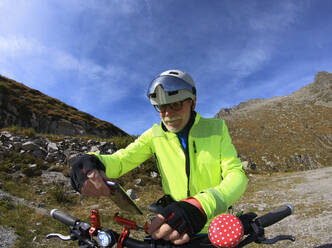 Senior man with his electric mountain bike in the Alps - LAF02384