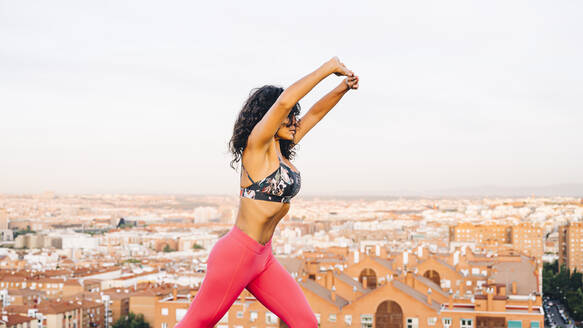 Woman performing abdominal hypopressive exercises outdoors - OCMF00816