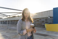 Portrait of young woman with coffee to go and mobile phone at backlight - AFVF04082