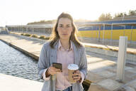 Portrait of serious young woman with mobile phone and coffee to go - AFVF04085