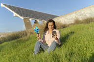 Portrait of smiling young woman sitting on a meadow with pinwheel looking at mobile phone - AFVF04091
