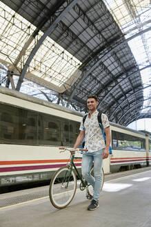 Man pushing bicycle through a station - JNDF00129