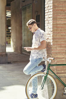 Man with bicycle leaning against a wall using his smartphone - JNDF00144