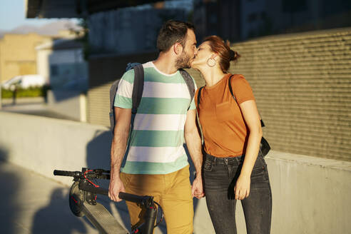Spain, Andalusia, Granada. Young couple using electric scooters kissing in urban street. Lifestyle concept. - JSMF01355