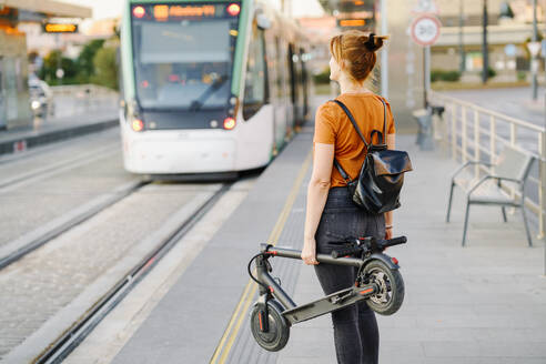 Back view of woman with backpack and folded electric scooter waiting at tram stop - JSMF01361