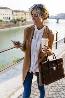 Smiling woman with coffee to go using smartphone in the city - GIOF07308