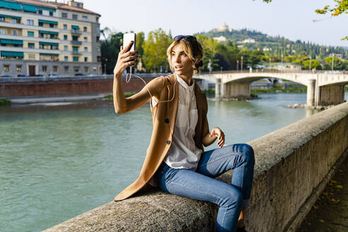 Woman with earphones sitting at riverside taking a selfie - GIOF07314