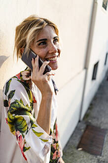 Smiling woman using smartphone in the city outdoors - GIOF07323