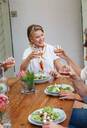 Woman toasting at lunch with friends in restaurant - ISF22255